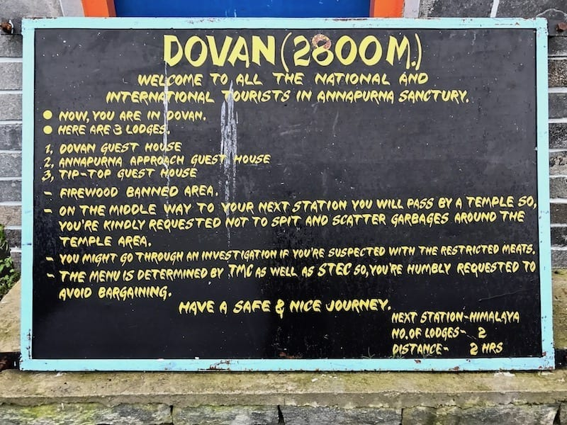 Trekking information sign in Dovan | Annapurna in the Monsoon Day 6: The Shrine of Dovan | nepal temple in Annapurna Sanctuary | ABC trek | Asian female trekking | Teja on the Horizon