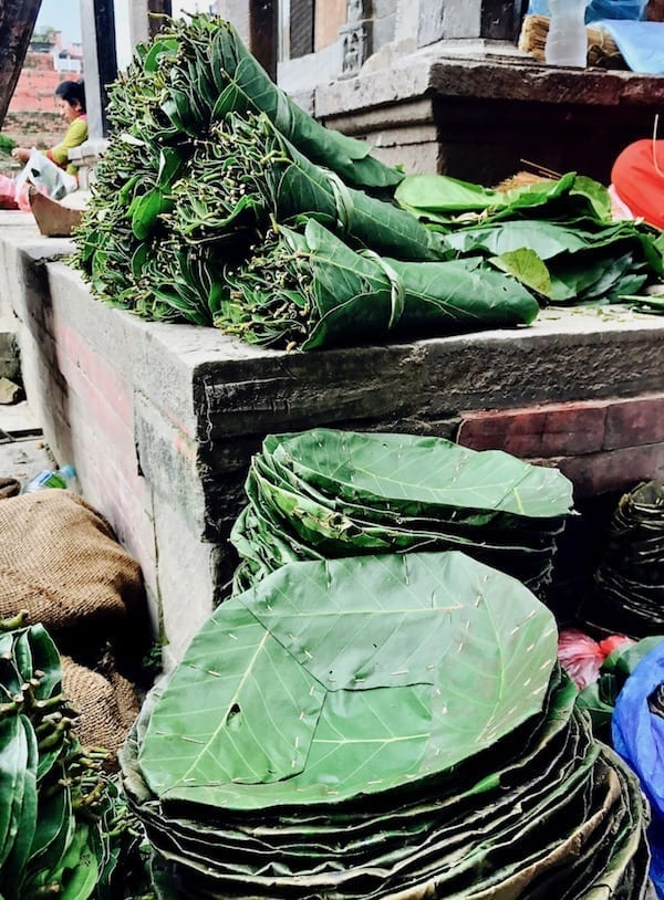 Stacks of leaves being turned into plates in Kathmandu Durbar square | sustainable travel | responsible travel | eco-friendly travel | travel tips | ethical travel | mindful travel | slow travel | Travel Sustainably Nepal edition How I Tried to Travel Responsibly | Teja on the Horizon