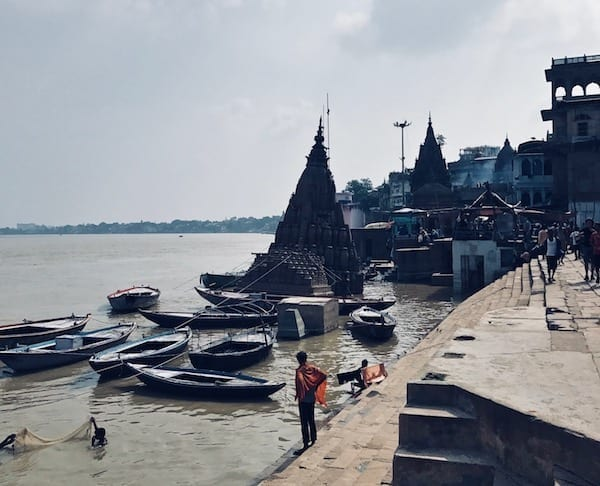 The cremation platforms and sunken Shiva temple in the distance from Manikarnika Ghat, Varanasi, India | solo travel to Benaras | Header image for travel story My Varanasi Day Tour with a Shiva Devotee - The Burning Ghat on travel blog Teja on the Horizon