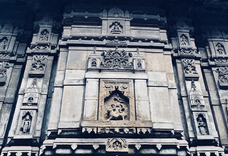 Shiva temple facade with carved stone in Varanasi, India | solo travel to Benaras | Header image for travel story My Varanasi Day Tour with a Shiva Devotee - Shiva City on travel blog Teja on the Horizon