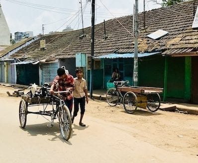 Boys walking by a trishaw wagon on a dirt street in the outskirts of Varanasi, India | Street view en route to Sarnath on a day trip from Benaras