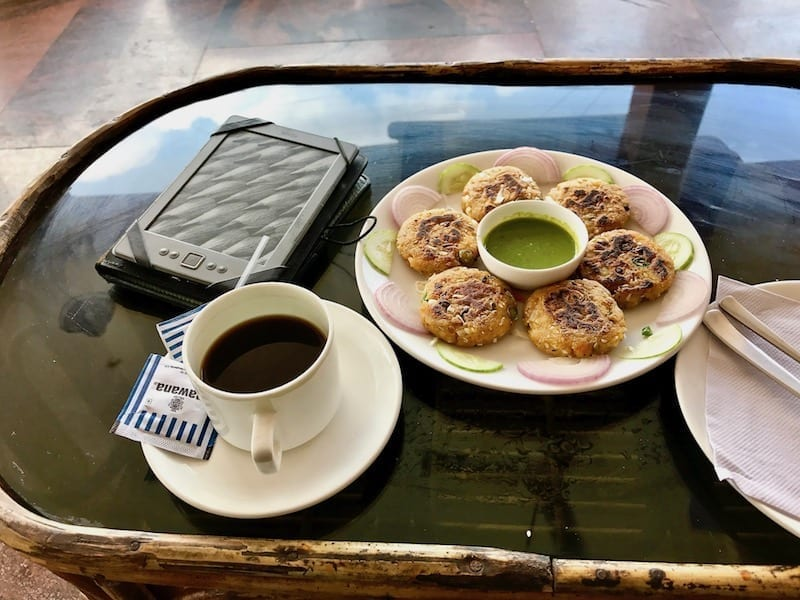 Snacks and coffee with a Kindle on a cafe table in Sheroes' Hangout, Lucknow, India