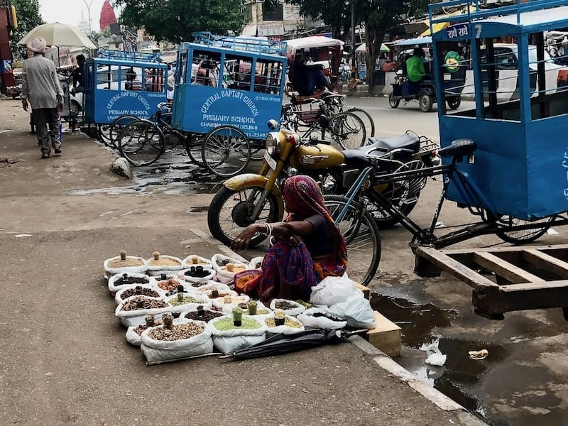 Indian woman sitting on the public footpath in New Delhi selling spices | Delhi walking tour