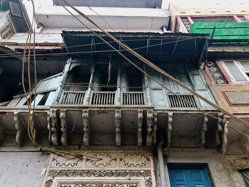 Looking up to a faded blue old wooden balcony in a Delhi side street | sights from a Delhi walking tour