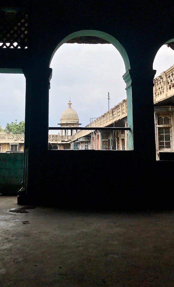 View from within a neglected building in Delhi, through an arched window, looking to a rooftop domed gazebo