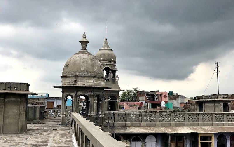 View along a Delhi rooftop looking towards an old domed gazebo, against a backdrop of dark raincloud | Delhi walking tour