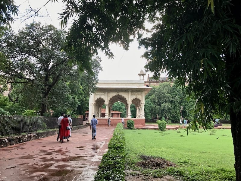 View of the white marble Bhadon Pavilion down a red brick path in the gardens of the Red Fort of Delhi