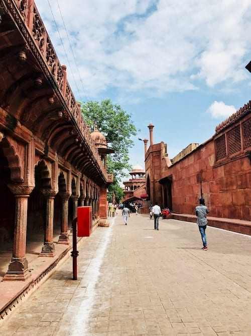 Agra street leading to the Taj Mahal East Gate, flanked by graceful arched pedestrian covered path on the left and red stone wall on the right