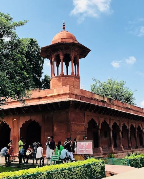 What the way to the Taj Mahal water filling station looks like - red stone scalloped archways topped by graceful mini domed watch tower