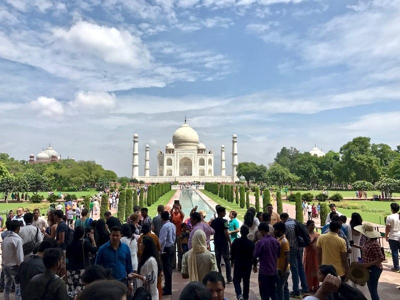 Late morning crowd entering the Taj Mahal gardens on Eid-ul Adha with the Taj Mahal in the distance against blue sky | UNESCO Heritage Site of Agra, India