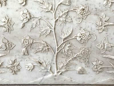Floral bas-relief marble carving on the Taj Mahal framed by a pietra dura border