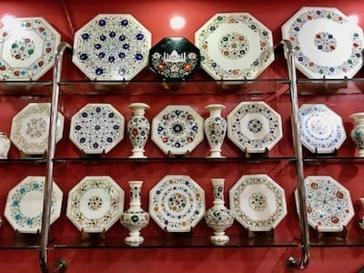 Decorative marble inlay plates and vases on a display shelf for sale in Agra | Taj Mahal Mughal marble craft in present day