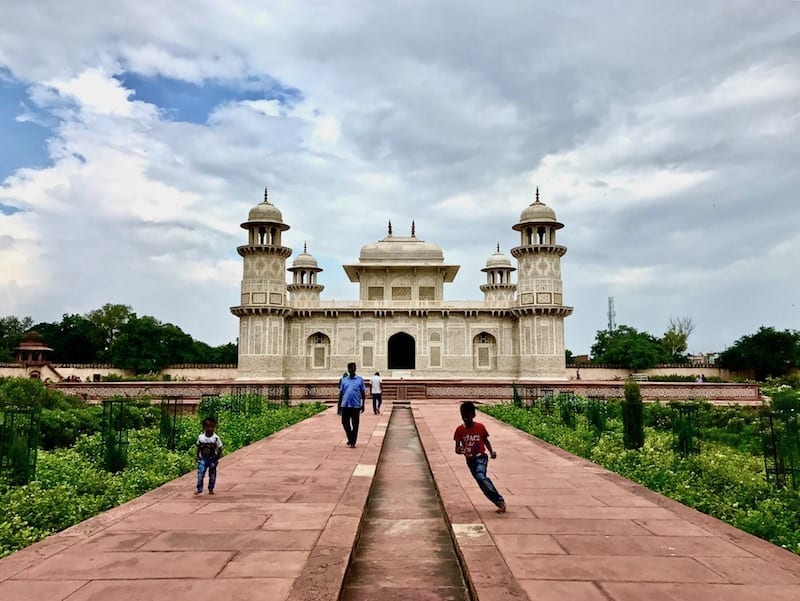 Children running at play within the mausoleum gardens of the Tomb of I'timad ud-Daula in Agra, India | Family tomb built by Mughal Empress Nur Jahan