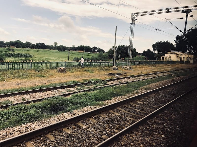 View of Indian railway train tracks against countryside from inside a train cabin | Travel sustainably by taking the train