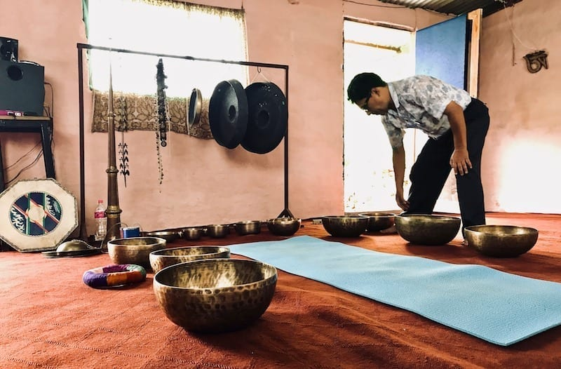 The singing bowl music master busy laying his instruments around the yoga mat where the person undergoing sound therapy would lie down | Nepali sound massage using Himalayan singing bowls