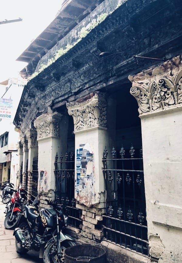 Motorcycles resting against decorated columns of an old Varanasi building