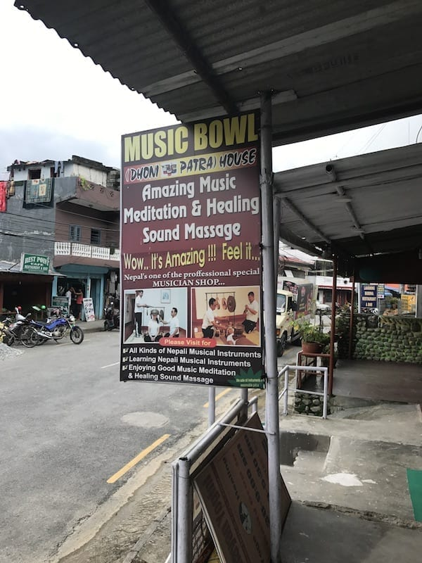 Sign advertising a music bowl shop and sound massage services at the Lakeside street in Pokhara, Nepal | Sound therapy using Nepali singing bowls | Himalayan music culture