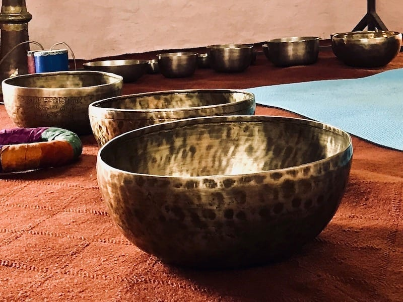 Large alloy metal Tibetan singing bowls laid out in preparation for sound therapy session in Pokhara, Nepal | Teja on the Horizon blog travel story