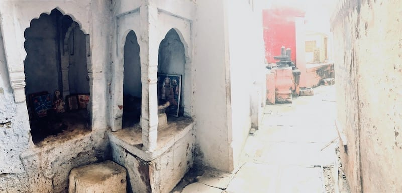 Altar nook to Shiva in a Varanasi alleyway, and Shiva lingas further down the alley | View while wandering the warrens of Varanasi's old city