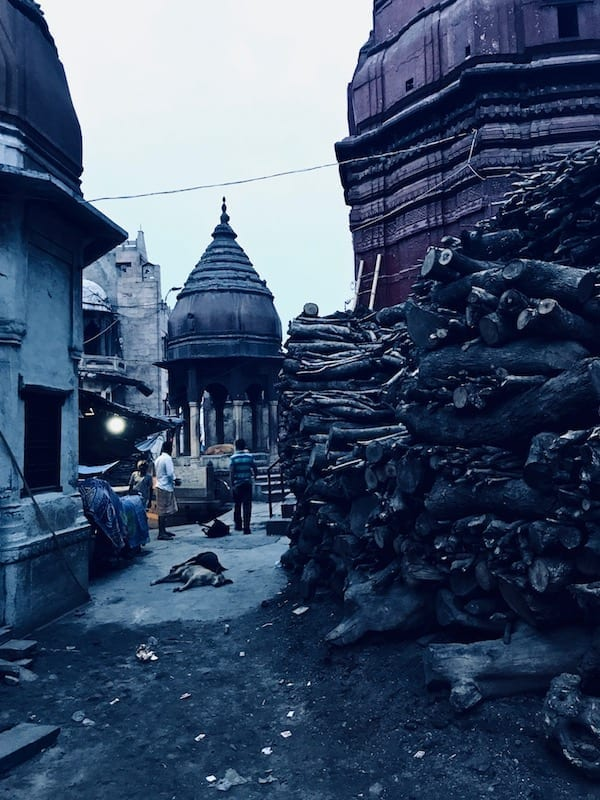 Path to Manikarnika ghat passing by a high stack of wood for the cremation pyres of the burning ghat   View while wandering the alleys of old Varanasi