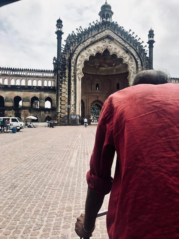 View of my rickshaw driver cycling towards the Rumi Darwaza gate in old Lucknow, capital of Uttar Pradesh, India.