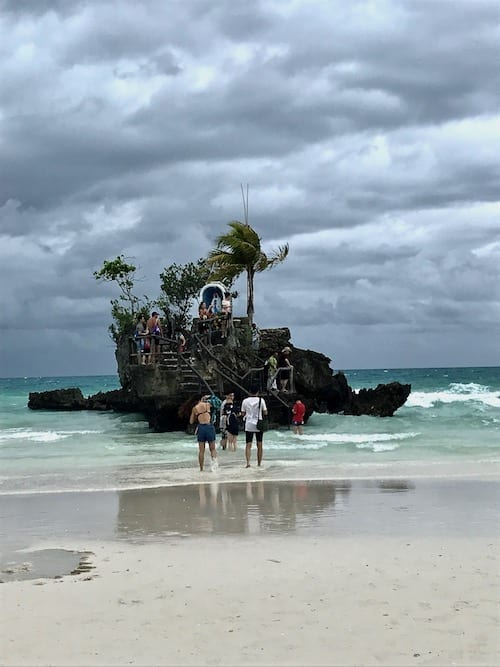Boracay visitors walking up to a little Catholic shrine of the Virgin Mary on a little rock outcrop along Station 1 beach of Boracay, against an overcast sky during the Philippines typhoon season.