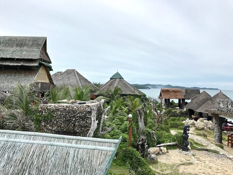 A view from high ground in Crystal Cove Resort looking over the thatched roofs of buildings within the complex | Boracay day tour