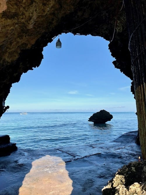 A view out to a rock outcrop against the sea background through an island rock arch at the end of Station 1 beach, Boracay