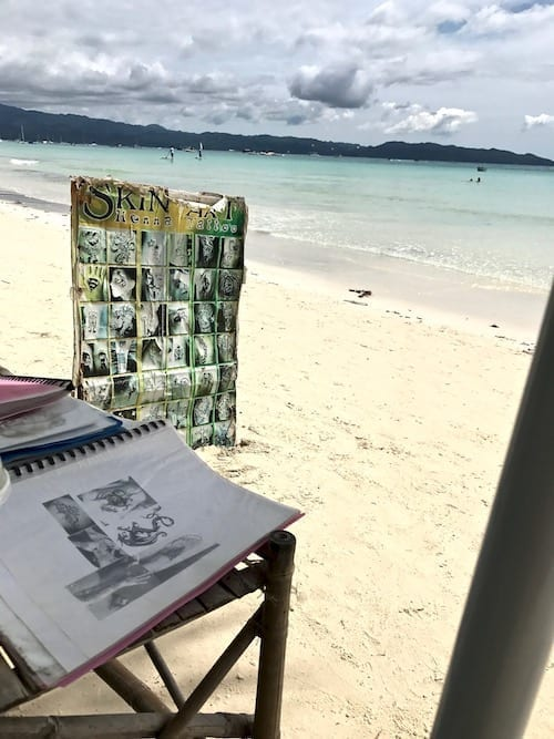 Henna tattoo artist's shack on Station 1 beach boracay, looking through tattoo catalogs and looking out to Station 1 beach on Boracay