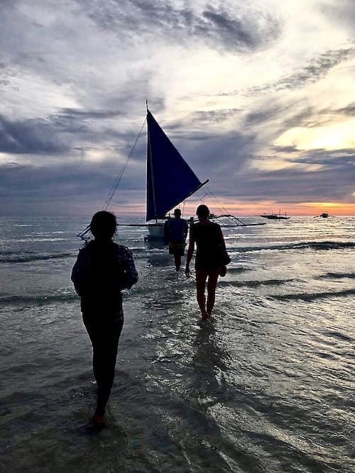 Silhouette of people walking through the shallows to a Philippine outrigger boat to sail to the sunset | Boracay, Philippines