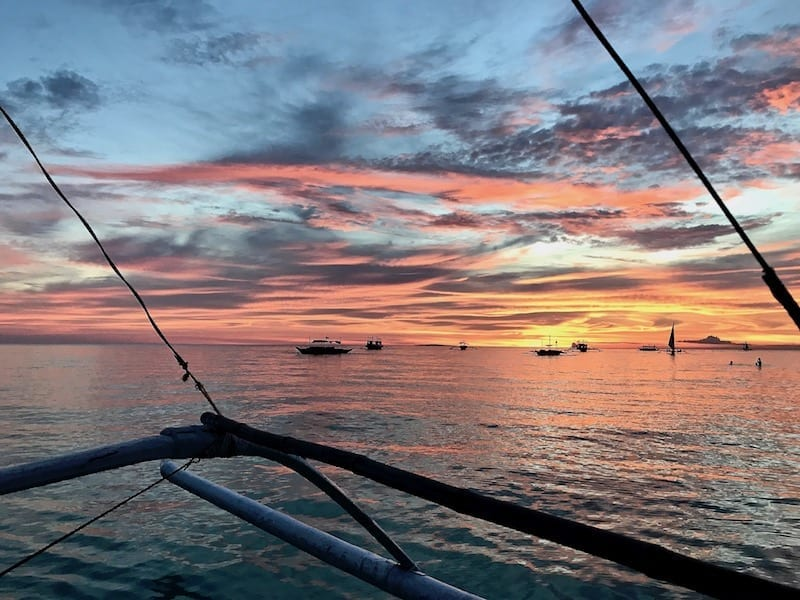 View of incredible orange and gold sunset with molten cloud effect over the sea horizon of Boracay viewed from an outrigger boat | Is Boracay worth going in the off season