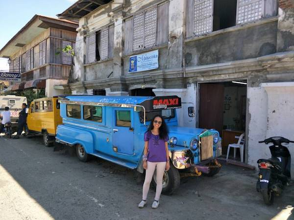 In front of a bright blue jeepney in UNESCO Heritage City of Vigan, Ilocos Sur, Philippines
