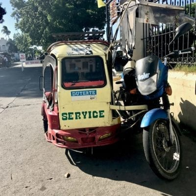 Yellow and red trike with Duterte sticker | default transportation in Vigan